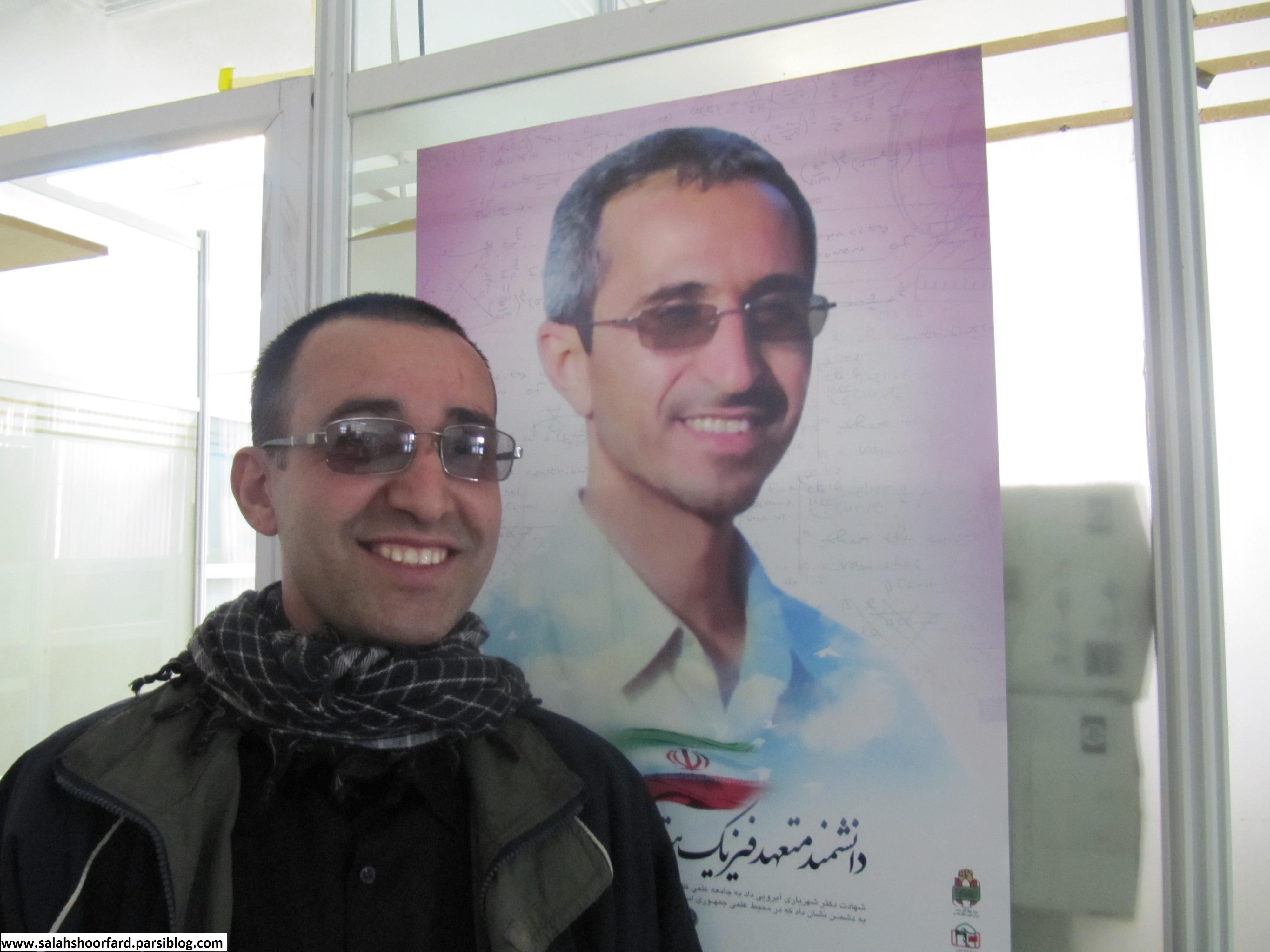 یکی از کارکنان دانشگاه شاهد در کنار پوستر شهید شهریاری